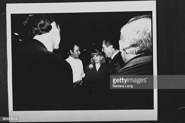 Sen. Bob Krueger w. Wife Kathleen Tobin Krueger shaking hands & chatting w. Four unident. Men at campaign function at the Jefferson County...