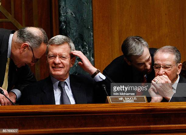 Sen Charles Schumer confers with committee chairman Sen Max Baucus as an aide confers with Sen Chuck Grassley during testimony by Secretary of Health...