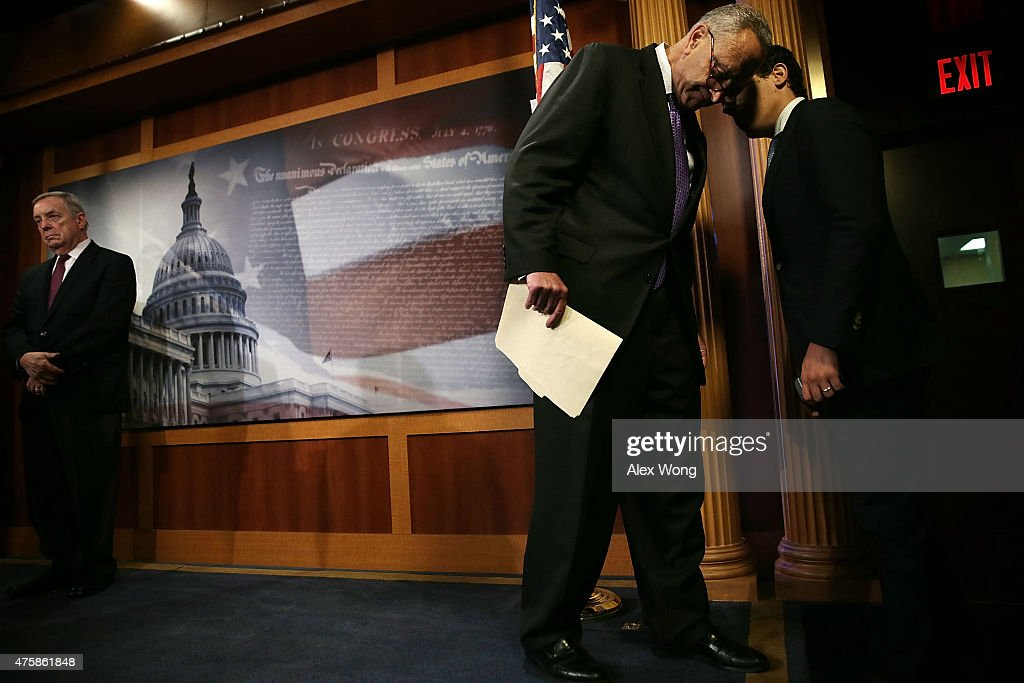 U.S. Sen. Charles Schumer (D-NY) (2nd L) listens to an aide as he participates in a news conference with Senate Minority Whip Sen. Richard Durbin (D-IL) (L) June 4, 2015 on Capitol Hill in Washington, DC. The senators held a news conference to discuss the National Defense Authorization Act.