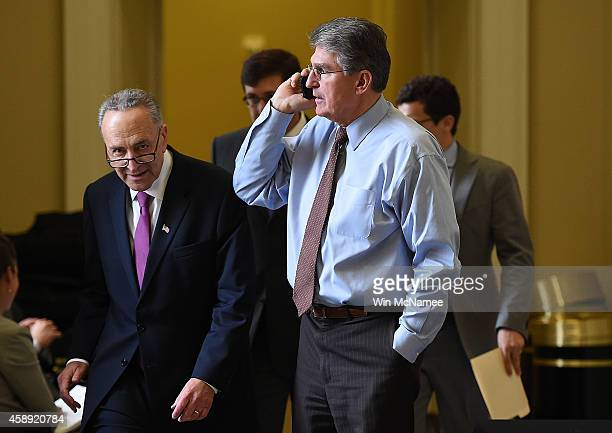 Sen Charles Schumer passes Sen Joe Manchin as Manchin speaks on the phone outside the room where Democrats met for their weekly policy luncheon at...