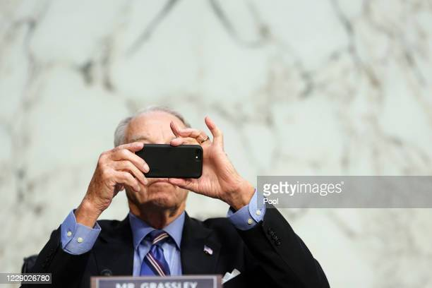Sen. Chuck Grassley , uses his phone during Supreme Court Justice nominee Judge Amy Coney Barrett's Senate Judiciary Committee confirmation hearing...