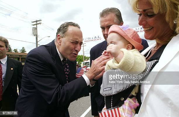 Sen Chuck Schumer stops to greet a tot while marching in the Memorial Day Parade in Douglaston Queens
