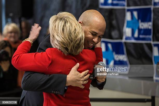 Sen Cory Booker hugs Democratic presidential candidate Hillary Clinton at a campaign event at Vernon Middle School on January 24 2016 in Marion Iowa...