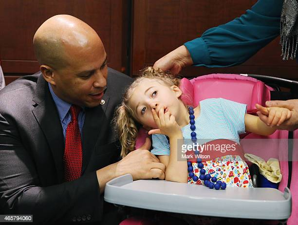 S Sen Cory Booker kneels near fouryearold Morgan Hintz who suffers from a rare form of epilepsy during a news conference on medical marijuana on...