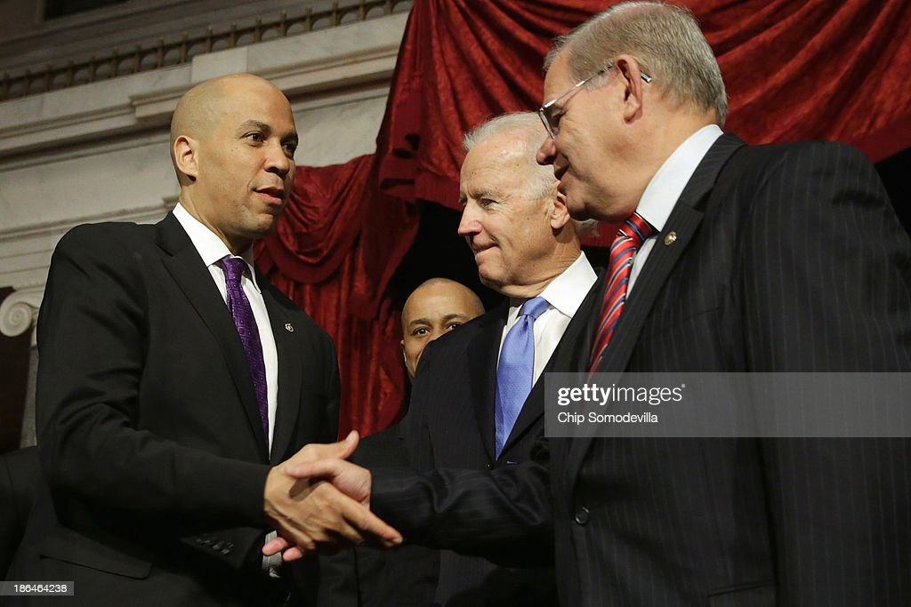Sen. Cory Booker (D-NJ) (L) shakes hand with Sen. Robert Menendez (D-NJ) after Booker's ceremonial swearing-in with Vice President Joe Biden (C) in the Old Senate Chamber at the U.S. Capitol October 31, 2013 in Washington, DC. Booker defeated Republican Steve Lonegan in a special election to replace Frank Lautenberg, who died in June.