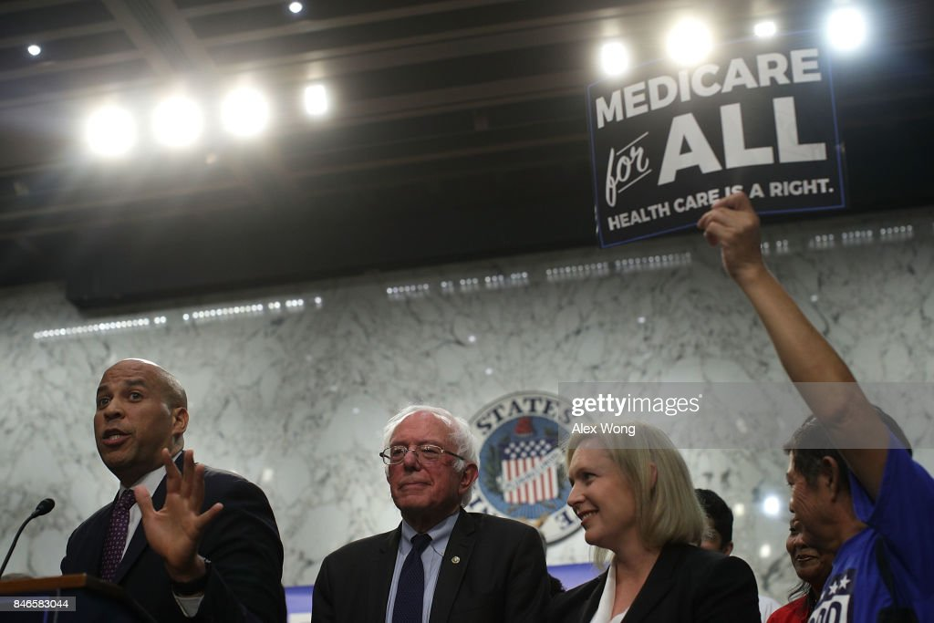 U.S. Sen. Cory Booker (D-NJ) speaks as Sen. Bernie Sanders (I-VT) and Sen. Kirsten Gillibrand (D-NY) listen during an event on health care September 13, 2017 on Capitol Hill in Washington, DC. Sen. Sanders held an event to introduce the Medicare for All Act of 2017.