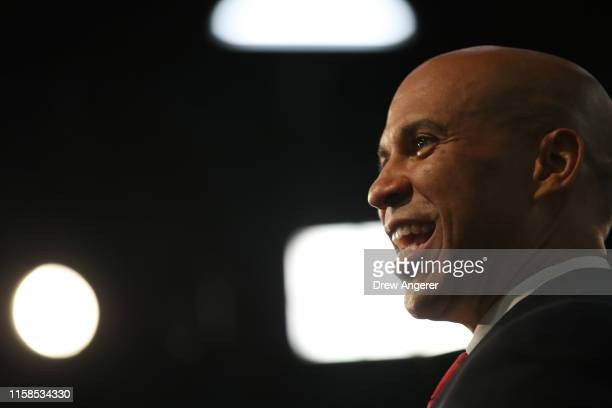 Sen Cory Booker speaks to the media in the spin room following the first night of the Democratic presidential debate on June 26 2019 in Miami Florida...