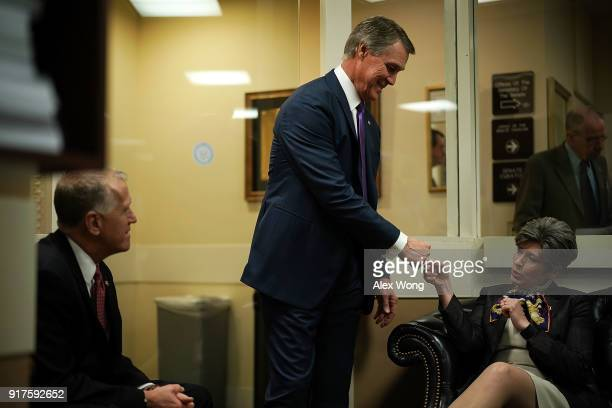 S Sen David Perdue fistbumps Sen Joni Ernst as Sen Thom Tillis looks on prior to a news conference on immigration February 12 2018 at the Capitol in...