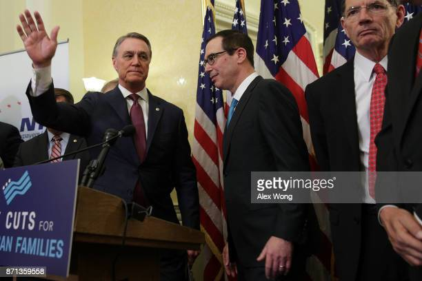 US Sen David Perdue Secretary of the Treasury Steven Mnuchin and Sen John Barrasso attend a news conference on tax reform November 7 2017 on Capitol...