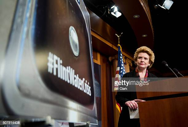 Sen Debbie Stabenow DMich looks at poster showing dirty water in Flint Michigan as she arrives for the Senate Democrats' news conference on the lead...