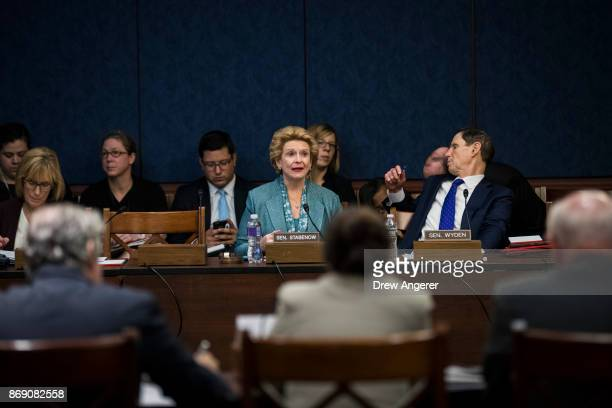 Sen Debbie Stabenow speaks as Sen Ron Wyden talks to an aide during a meeting about the GOP tax plan held by the Democratic Policy and Communications...