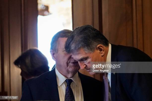 Sen. Dick Durbin speaks with Sen. Joe Manchin as they exit a lunch meeting with fellow Senate Democrats before heading to the Senate impeachment...