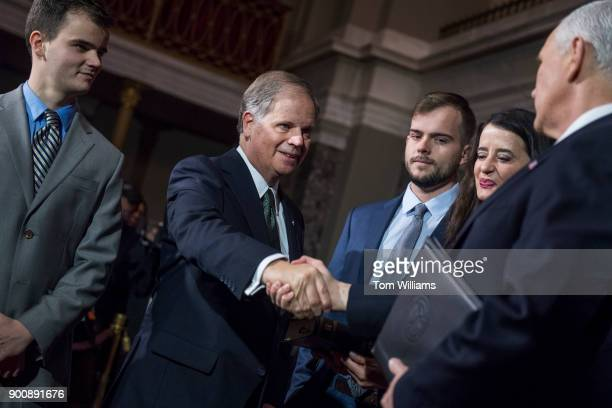 Sen Doug Jones DAla is administered an oath by Vice President Mike Pence during a swearingin ceremony in the Capitol's Old Senate Chamber after the...