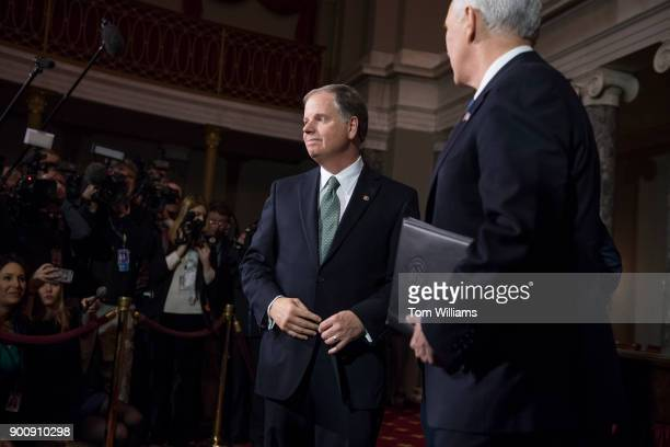 Sen Doug Jones DAla is seen after being administered an oath by Vice President Mike Pence right during a swearingin ceremony in the Capitol's Old...