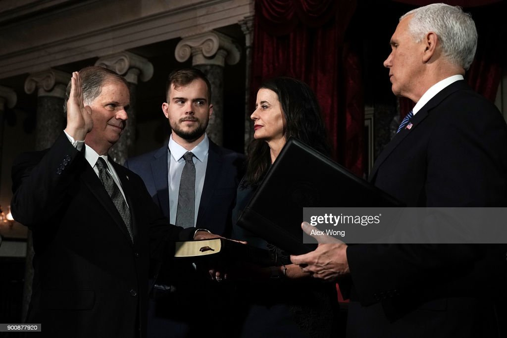 U.S. Sen. Doug Jones (D-AL) (L) participates in a mock swearing-in ceremony with Vice President Mike Pence (R) as Jones' wife Louise (3rd L) and son Carson (2nd L) look on at the Old Senate Chamber of the U.S. Capitol January 3, 2018 in Washington, DC. Jones is the first Democratic senator from Alabama in more than two decades. He defeated Roy Moore leaving Republicans with a 51-49 majority in the U.S. Senate.