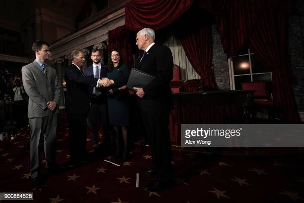 S Sen Doug Jones shakes hands with Vice President Mike Pence as Jones' wife Louise sons Carson and Christopher look on during a mock swearingin...