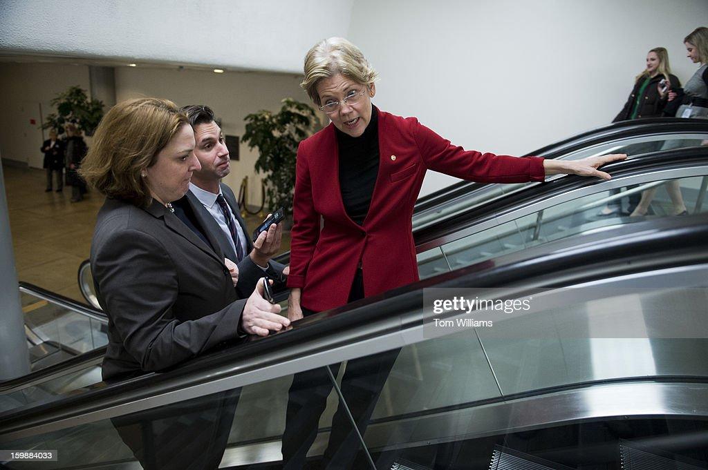 Sen. Elizabeth Warren, D-Mass., talks with reporters in the senate subway before the senate luncheons in the Capitol.