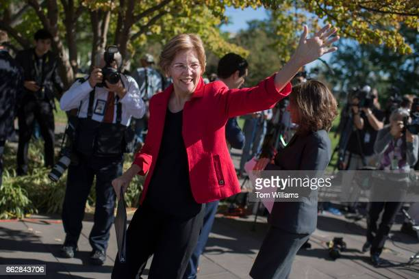 Sen Elizabeth Warren DMass waves to tourists after a news conference on the east lawn of the Capitol on a CAP Action report saying that wealthy...