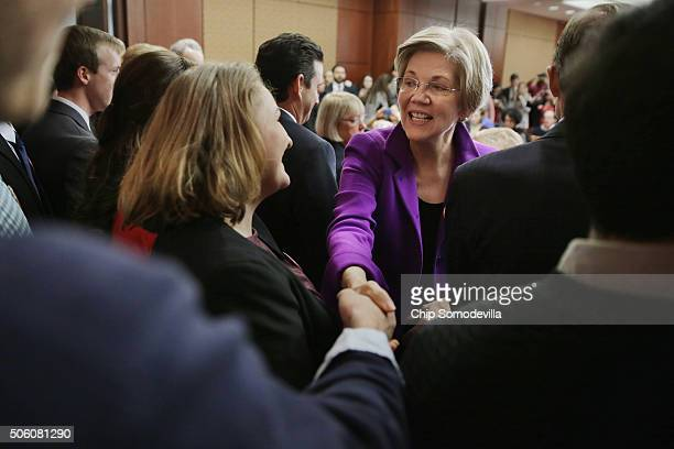 Sen Elizabeth Warren greets college students before a news conference to unveil a legislative package to address college affordability in the US...