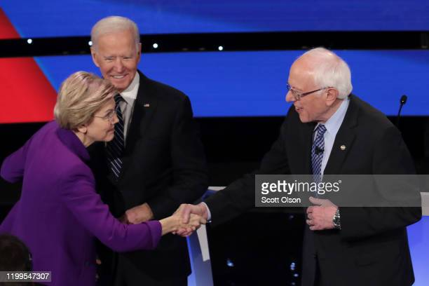 Sen Elizabeth Warren greets Sen Bernie Sanders as former Vice President Joe Biden looks on ahead of the Democratic presidential primary debate at...