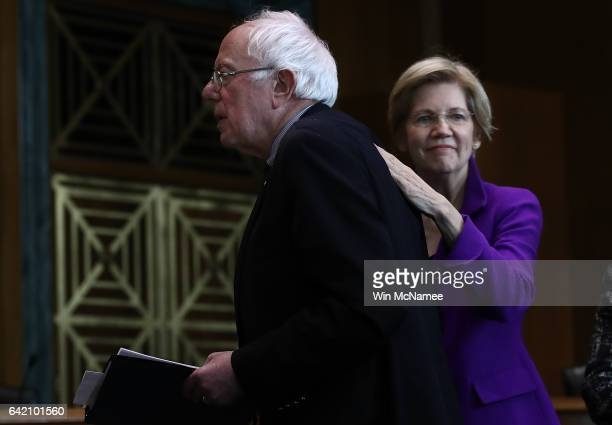 Sen Elizabeth Warren pats Sen Bernie Sanders on the back after Sanders spoke at a news conference on the Social Security system February 16 2017 in...
