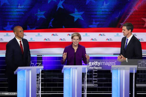 Sen Elizabeth Warren speaks as Sen Cory Booker and former Texas congressman Beto O'Rourke look on during the first night of the Democratic...