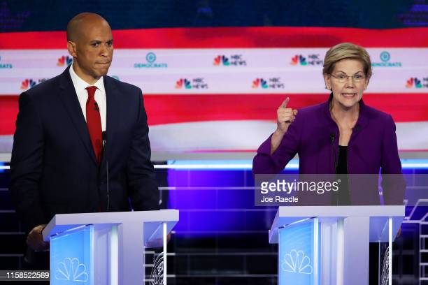 Sen Elizabeth Warren speaks as Sen Cory Booker looks on during the first night of the Democratic presidential debate on June 26 2019 in Miami Florida...