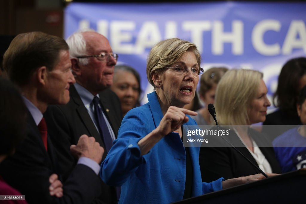 U.S. Sen. Elizabeth Warren (D-MA) (C) speaks on health care as Sen. Bernie Sanders (I-VT) (2nd L) listens during an event September 13, 2017 on Capitol Hill in Washington, DC. Sen. Sanders held an event to introduce the Medicare for All Act of 2017.
