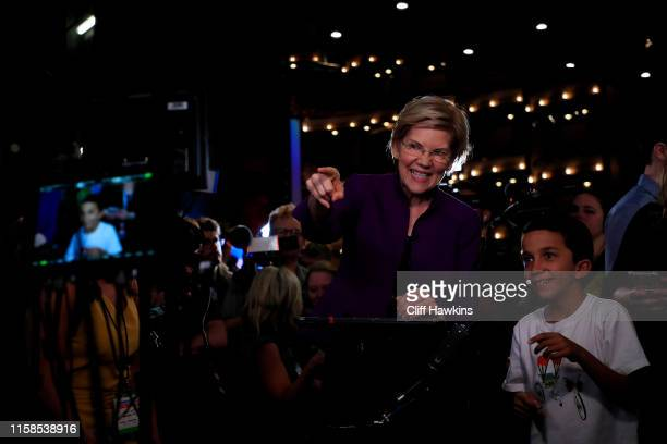Sen Elizabeth Warren speaks to the media in the spin room with her grandson by her side after the first night of the Democratic presidential debate...