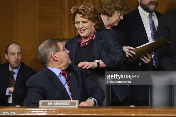 Sen Heidi Heitkamp greets Sen Robert Menendez before a hearing of the Senate Banking Housing and Urban Affairs Committee after the release of The...