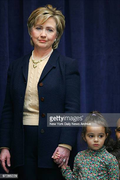 Sen Hillary Clinton holds the hand of 3yearold Camilla Harden during a news conference at the Ryan ChelseaClinton Community Heath Center on 10th Ave...