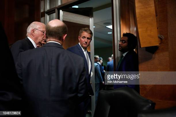 Sen Jeff Flake confers with Democratic senators Sen Patrick Leahy and Sen Chris Coons while leaving a Senate Judiciary Committee meeting in the...
