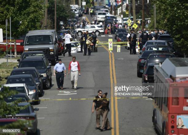 Sen Jeff Flake of Arizona walks along the road as Alexandria police and emergency members gather near the crime scene of an early morning shooting in...
