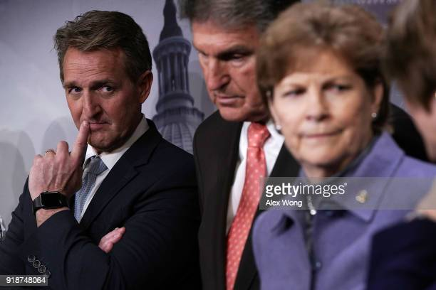 US Sen Jeff Flake Sen Joe Manchin and Sen Jeanne Shaheen listen during a news conference February 15 2018 at the Capitol in Washington DC The...