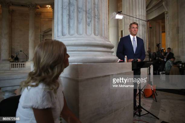 Sen Jeff Flake speaks to reporters on Capitol Hill after announcing he will not seek reelection as his wife Cheryl watches October 24 2017 in...
