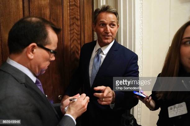 Sen Jeff Flake talks briefly with reporters after leaving the Senate Chamber at the US Capitol October 24 2017 in Washington DC Flake announced that...