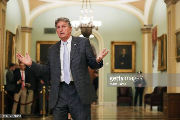 Sen. Joe Manchin gestures outside the Senate chamber during a recess in impeachment trial proceedings against President Donald Trump at the U.S....