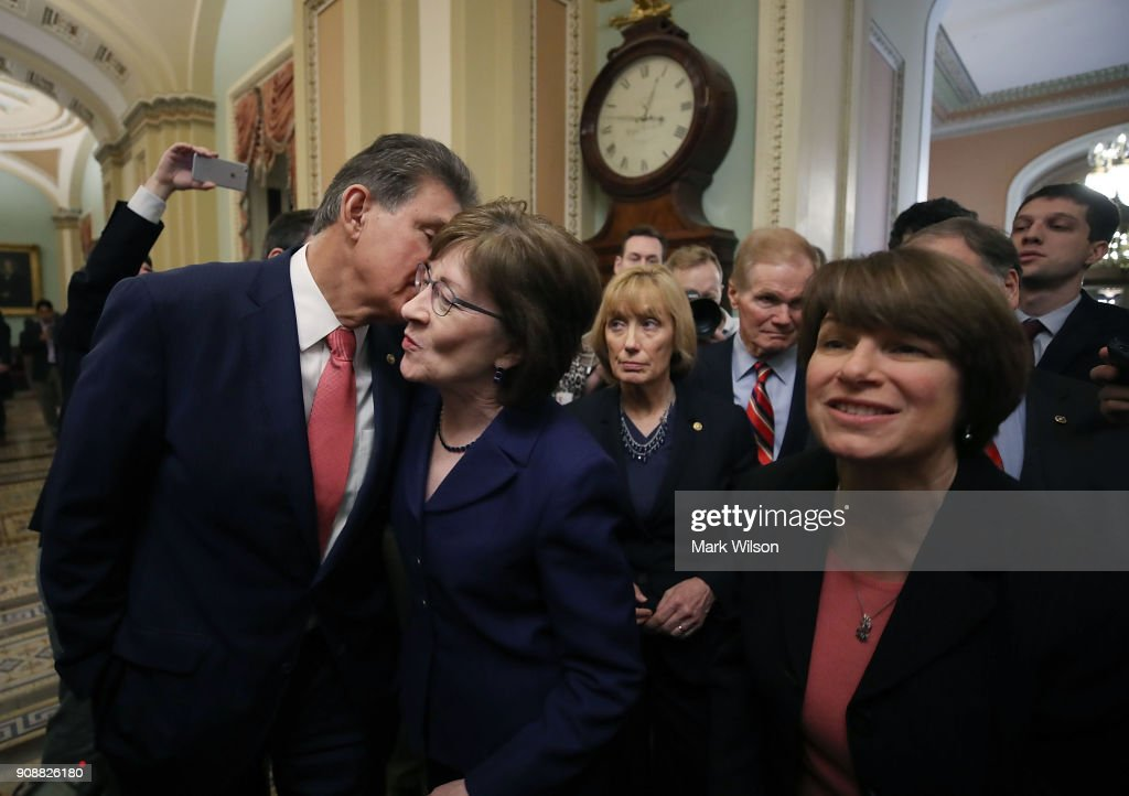 Sen. Joe Manchin (D-WV), (L), kisses Sen. Susan Collins (R-ME), (2ndL) as they celebrate with fellow Senators after the Senate voted and passed the a CR to reopen the government, at the U.S. Capitol on January 22, 2018 in Washington, DC. Senate leaders reached an arrangement to keep the government open until February 8.