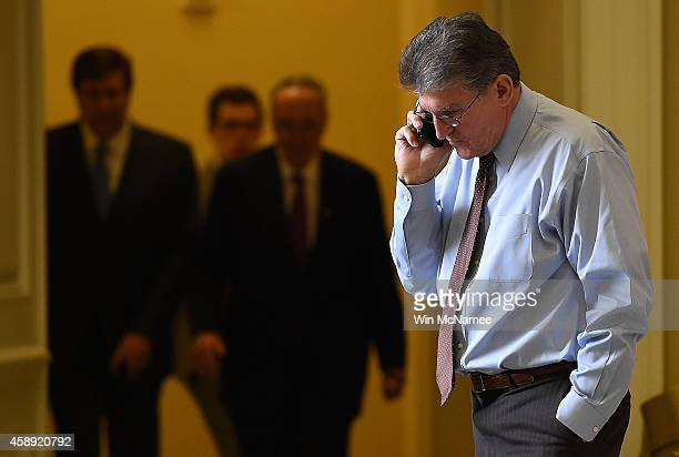 Sen Joe Manchin speaks on the phone outside the room where Democrats met for their weekly policy luncheon at the US Capitol November 13 2014 in...