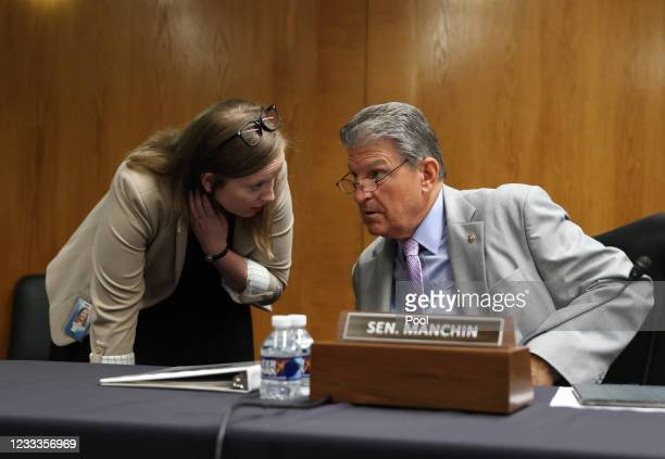 Sen. Joe Manchin, speaks with an aide before a Senate Appropriations Subcommittee with testimony by Xavier Becerra, Secretary of the Department of...