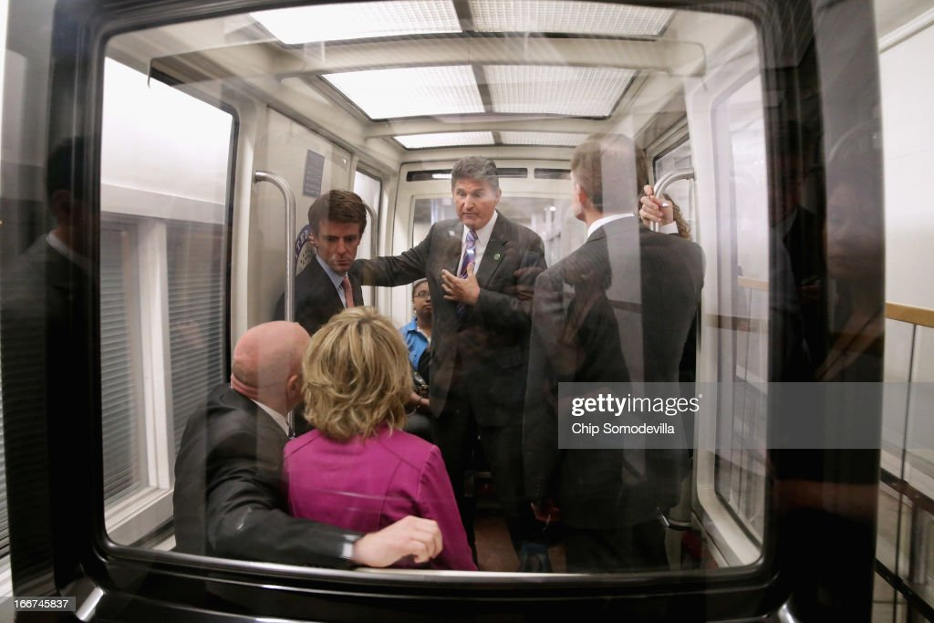 Sen. Joe Manchin (D-WV) (C) talks with shooting victim and former Rep. Gabrielle Giffords (D-AZ) (in pink) and her husband and retired astronaut Mark Kelly while riding the subway train between the Hart Senate Office Building at the U.S. Capitol with Sen. Pat Toomey (R-PA) (R) April 16, 2013 in Washington, DC. Giffords and Kelly met with members of Congress, including Manchin and Toomey, who have sponsored legislation to expand the background check system for gun sales.
