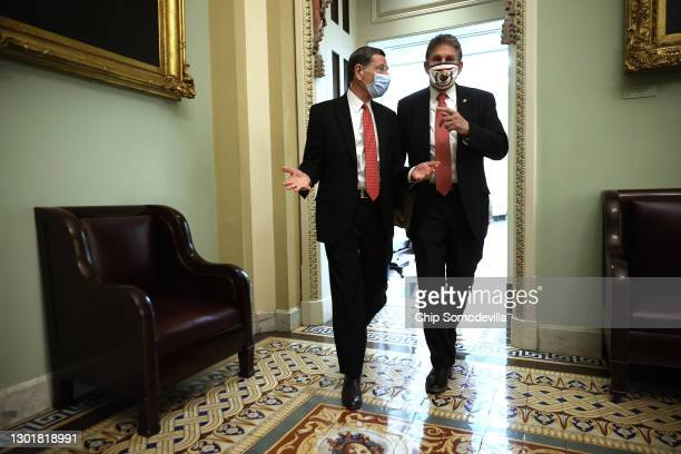 Sen. John Barrasso talks with Sen. Joe Manchin during a break in the fourth day of former President Donald Trump's impeachment trial at the U.S....