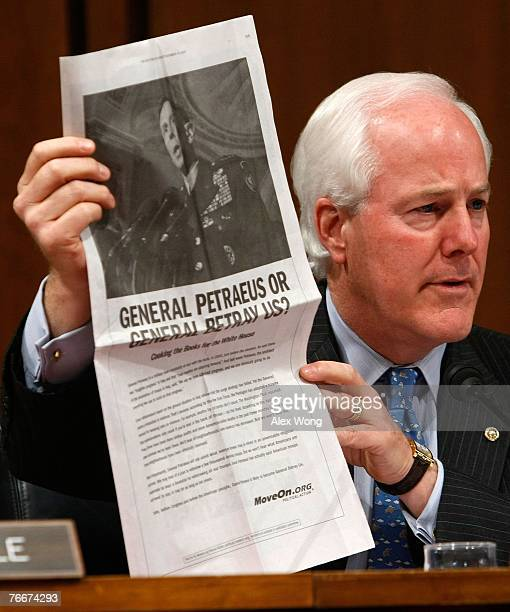 Sen John Cornyn holds up a copy of an ad paid for by MoveOnorg during a hearing of the Senate Armed Services Committee with General David Petraeus...