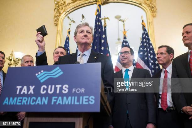 Sen John Kennedy RLa holds up his wallet during a news conference in the Capitol to illustrate that the families and small businesses would benefit...