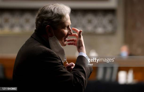S Sen John Kennedy pulls back his protective face mask to talk to another attendee during a Senate Judiciary Committee confirmation hearing on the...