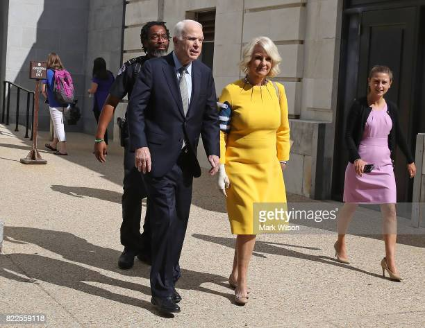 Sen John McCain and his wife Cindy McCain walk out of the Russell Senate Office building toward their car at the US Capitol July 25 2017 in...