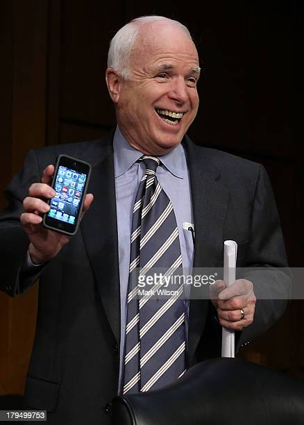 S Sen John McCain holds up his smart phone to show he is not playing poker before the Senate Foreign Relations Committee vote on a resolution on...