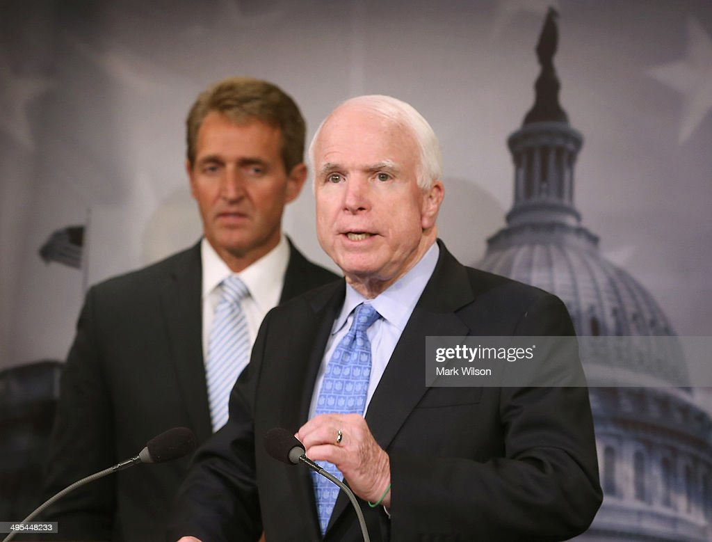Sen. John McCain (R-AZ) speaks while flanked by Sen. Jeff Flake (R-AZ) during a news conference on veterans affairs on Capitol Hill, June 3, 2014 in Washington, DC. The Senators introduced The Veterans Choice Act, which addresses issues raised by the scandal at the U.S. Department of Veterans Affairs, and provides veterans with greater flexibility and choice in health care providers and increasing accountability and transparency at the Veterans Affairs administration.