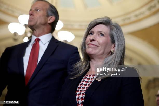 Sen. John Thune and Sen. Joni Ernst listen during a news conference following a policy luncheon at the Capitol Building on August 3, 2021 in...