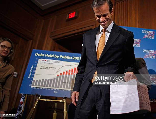Sen. John Thune lifts a copy of the Senate's proposed health care reform legislation after a news conference at the U.S. Capitol November 20, 2009 in...